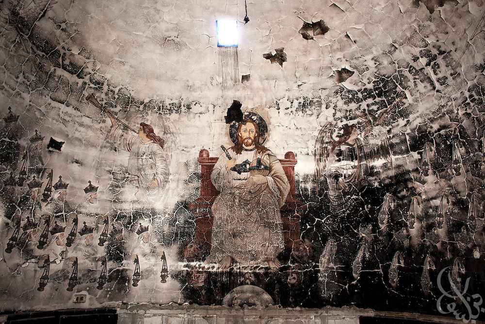 A fire damaged mural of Jesus is seen inside the Monastery of Emir Tadros church (est 1598) August 20, 2013 after a recent attack by Muslims in the village of Nazla, located near el Fayoum, around a 100 kilometers South of Cairo, Egypt.  Christian villagers report 2 churches and a monastery in the area came under attack by their Muslim neighbors on the same day as Egyptian security forces were moving to forcibly disperse the sit-in camp of the supporters of deposed president Mohamed Morsi.