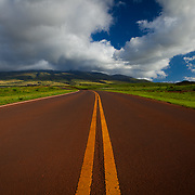 This Road is Near the Sugar Cain Train Area outside Lahiana, Maui HI. The road is stained red from all the volcanic dirt that is iron rich. On rainy days traffic lays it down on this road.