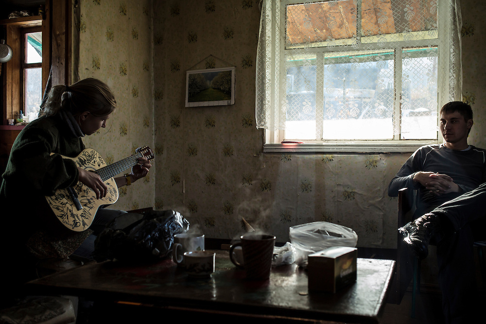 Marina Telezhnikova strums a guitar as Maxim Makarov, her boyfriend, listens on Sunday, October 27, 2013 in Baikalsk, Russia.