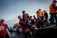 A volunteer  helps a young boy to land on the shore of Lesbos after crossing the Aegean sea. FEDERICO SCOPPA/CAPTA