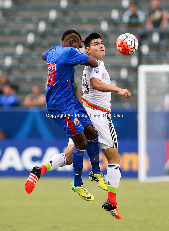 Haiti defender Severe Verilus, left, and Mexico midfielder Luis Guadalupe Loroña Aguilar fight for the head ball in the second half of a CONCACAF men's Olympic qualifying soccer match in Carson, Calif., Sunday, Oct. 4, 2015. Mexico won 1-0. (AP Photo/Ringo H.W. Chiu)