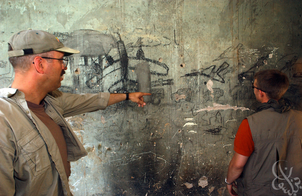 U. S. Army 489th Civil Affairs Battalion soldiers examine graffiti inside the ruins of the Kunduz Teachers' College June 7, 2002 in Kunduz, Afghanistan. The 489th Battalion is overseeing the reconstruction and equipping of the school, as well as numerous other humanitarian projects in the area as part of the ongoing Operation Enduring Freedom.