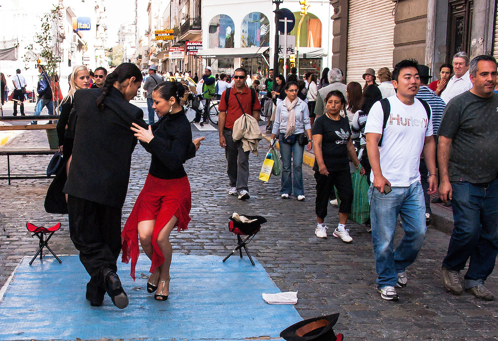 In San Telmo barrio, a couple dance the tango. But the by-passers seem to ignore them; only two or three people show any interest. Buenos Aires, Argentina.
