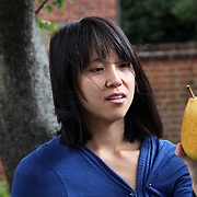 A woman holding a large pear, part of a fruit harvesting group in London