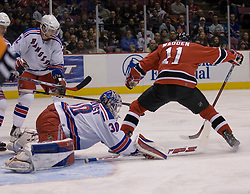 Feb 20, 2007; East Rutherford, NJ, USA; New Jersey Devils forward John Madden (11) skates battles with New York Rangers defenseman Henrik Lundqvist (30) during the first period at Continental Airlines Arena in East Rutherford, NJ.