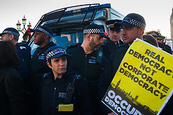 London, March 7th 2015. Following the Climate march through London, masked anarchists and environmental activists clash with police following a breakaway protest at Shell House. PICTURED: Met Police Territorial Support Group officers surround a van containing an arrested anti-fracking activist.