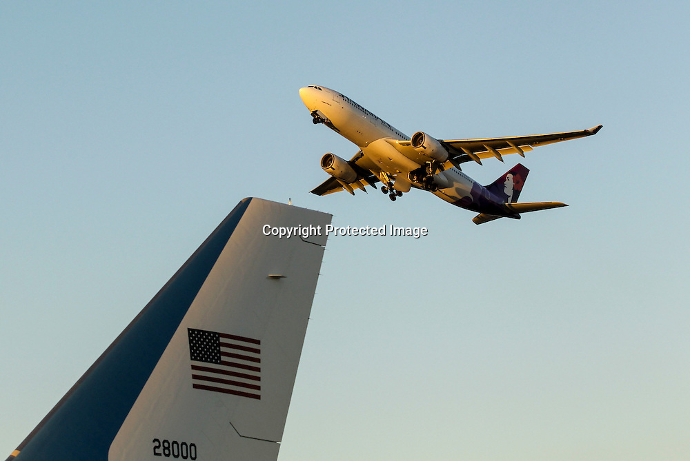 A Hawaiian Airlines aircraft flies past Air Force One sitting on the tarmac after landing at Los Angeles International Airport in Los Angeles on Saturday, Oct. 10, 2015.  (AP Photo/Ringo H.W. Chiu)