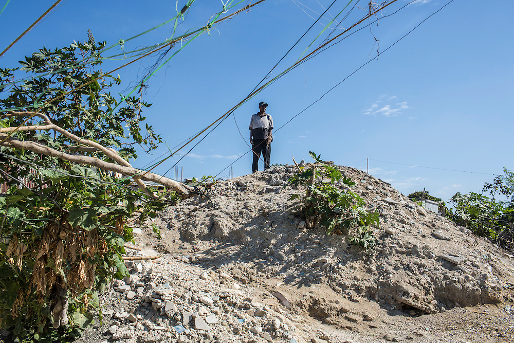 A man looks out from a hilltop in the Fort National neighborhood on Tuesday, December 16, 2014 in Port-au-Prince, Haiti. One of Port-au-Prince's poorer neighborhoods, Fort National was among the hardest hit by the 2010 earthquake. Still, its residents lack electricity or running water, and only several new homes have been built by the aid organizations and the government, despite years of promises.