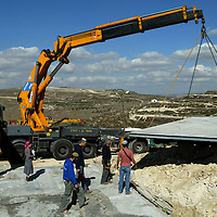 Israeli settlers lift up the floor part of a new caravan in a settlments of the West Bank on November 13. 2007. A law to prevent the extension of constructions in the West Bank forbids the transport of caravans on trucks. A group of settlers develloped a new technique, they build a caravan in several parts that they transport from a local factory and assemble them in the area that they choose. This new method give them the possibilty to transport the parts discretly through police and army checkpoints and build a caravan in one day. Photo by Olivier Fitoussi