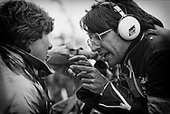 Jean-Pierre Jarier receives feedback from a Candy Team Tyrrell-Ford racing engineer during the 1979 United States Grand Prix. <br /> <br /> Communicating with one's fingertips was one of the few ways to convey complex handling interpretations during the late 1970's to the early 1980's.<br />  <br /> When driver's such as Jean Pierre Jarier left the pits, their only tools were their massive reflexes, their accumulated impressions and reports, and the best guesses of their engineer.<br /> <br /> On-board instrumentation and testing sensors to provide a clue about the somewhat crude ground-effect designs' tuning would not arrive for a few seasons, so for Jarier, it would need to be the art of using fingertips to represent the subtleties of lateral motion, cornering grip and balance as the drivers tried to find speed and avoid catastrophe. <br /> <br /> It is critical to note that these drivers and teams tested and raced without any confirmable data. There were no cad/cam advances, no fluid dynamics models, no wind tunnels. In fact there were no computers, no pit to driver communications, no simulators, no carbon fiber, no deformable structures, or Hans devices. <br /> <br /> Further, there were none of the safety and technological advances and aids that make today&rsquo;s F1 machines so incredibly safe.