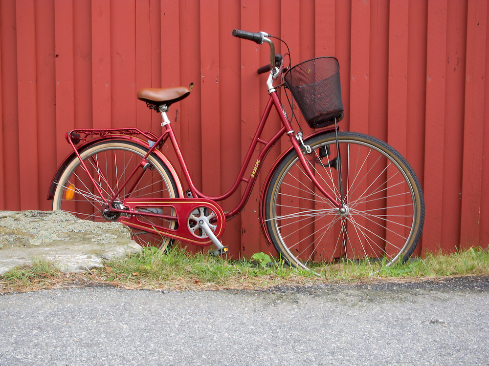 A maroon coloured bike leans against a similar coloured wall in Kladesholmen, Sweden.