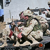 A wounded U.S. soldier is evacuated on the front of a humvee as it races away from an Iraqi police station in central Baghdad, Iraq. The police station came under attack by insurgents using mortars launched from a nearby apartment building. The wounded soldier lost her arm in the attack. May 2004
