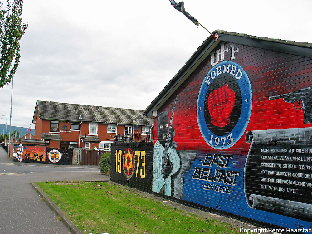 """Protestant murals on Newtownards Road in East Belfast. The Ulster Defence Association (UDA) is a loyalist paramilitary group in Northern Ireland. It was formed in September 1971 and undertook an armed campaign of almost twenty-four years during """"The Troubles"""". Most UDA attacks were carried out using the name Ulster Freedom Fighters (UFF). It is classified as a terrorist group in the United Kingdom. Belfast wall paintings can be both Loyalist and Republican in content. These murals are from the loyalist Newtownards Road. Northern Ireland, Nord-Irland, Belfast, Europe, country, land, war, struggle, island,"""
