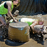 .One of the favorite events at the Stoughton Fair is Pig Wrestling. This timed event has teams of four attempt to pick up a pig,  and place it on top of a rubber container..The water filled mud ring makes the event a bit harder. The competition was held Sunday July 8, 2012.
