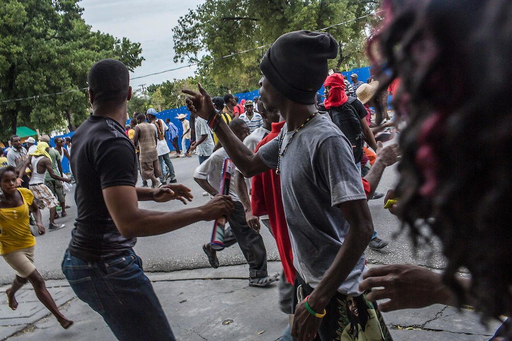 Protesters run from tear gas during an anti-government demonstration on Tuesday, December 16, 2014 in Port-au-Prince, Haiti. President Michel Martelly was elected in 2010 with great hope for reforms, but in the wake of slow recovery and parliamentary elections that are three years overdue, his popularity has suffered tremendously, forcing Prime Minister Laurent Lamothe to resign.