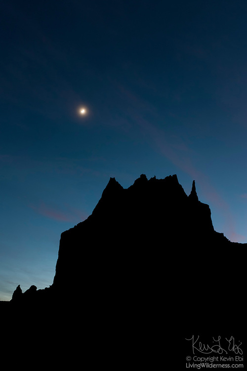 """The crescent moon hovers over Shiprock, a prominent peak in northwestern New Mexico. Early European settlers thought the peak resembled a sailing schooner. The Navajo people, who settled the area first, called it """"Rock with Wings."""" Their legend states a great bird guided them from the North to settle in the present-day Four Corners area of the United States near where this peak is located."""