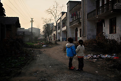 Children from Xiangnan Village look at their village houses blackened by pollution from a nearby chemical plant in Zekou Town, Qianjiang City of Hubei Province, China 14 January 2013. Many of the young villagers have moved out or tried to move out of their polluted villages. Those who could not fear for their children's health and wish the government could help them relocate their homes away from the villages. While the heavy smog in Beijing and much of northern China in recent days have caused alarm among residents and renewed scrutiny on the pollution woes of the country, villagers in a small town of Hubei Province have been grappling with severe air, water and noise pollution on a daily basis over the past two years. China's Xinhua news reported 04 January 2013 that more than 60 cancer deaths in various villages of Zekou Town has been caused by the heavy pollution from the chemical industry park nearby. About 20 or more chemical plants built around the villages of Dongtan, Xiangnan, Zhoutan, Sunguai, Qingnian and others over the past two years has created huge increases in noise, air and water pollution. Many villagers complained of intensifying respiratory, heart, skin and circulatory illnesses caused by the pollution and a large spike in cancer diagnoses and deaths since the factories were built. .