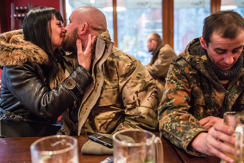 Vika (L) kisses her friend Kolya (C) as fellow soldier Sergei drinks a beer at a local pizza restaurant after their unit withdrew from Debaltseve on February 19, 2015 in Artemivsk, Ukraine. Ukrainian forces have begun withdrawing from the strategic and hard-fought town of Debaltseve after being effectively surrounded by pro-Russian rebels.