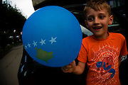 Albanian boy on the streets of Mitrovica, Kosovo with a Kosovo Flag balloon.