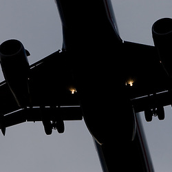 The underside of a jet plane as it approaches the runway.