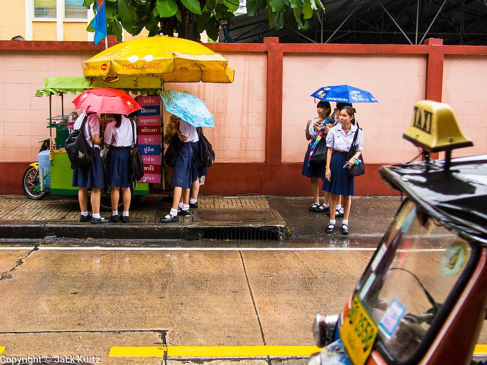 20 SEPTEMBER 2013 - BANGKOK, THAILAND:   Girls from Sai Nam Pueng School on Soi 22 Sukhmvit, wait for taxi during a rain storm in Bangkok.     PHOTO BY JACK KURTZ