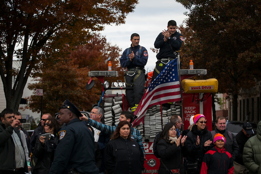 Firefighters and other spectators cheer participants along 4th Ave in the New York City Marathon in Brooklyn, NY on Sunday, Nov. 3, 2013.<br /> <br /> CREDIT: Andrew Hinderaker for The Wall Street Journal<br /> SLUG: NYSTANDALONE