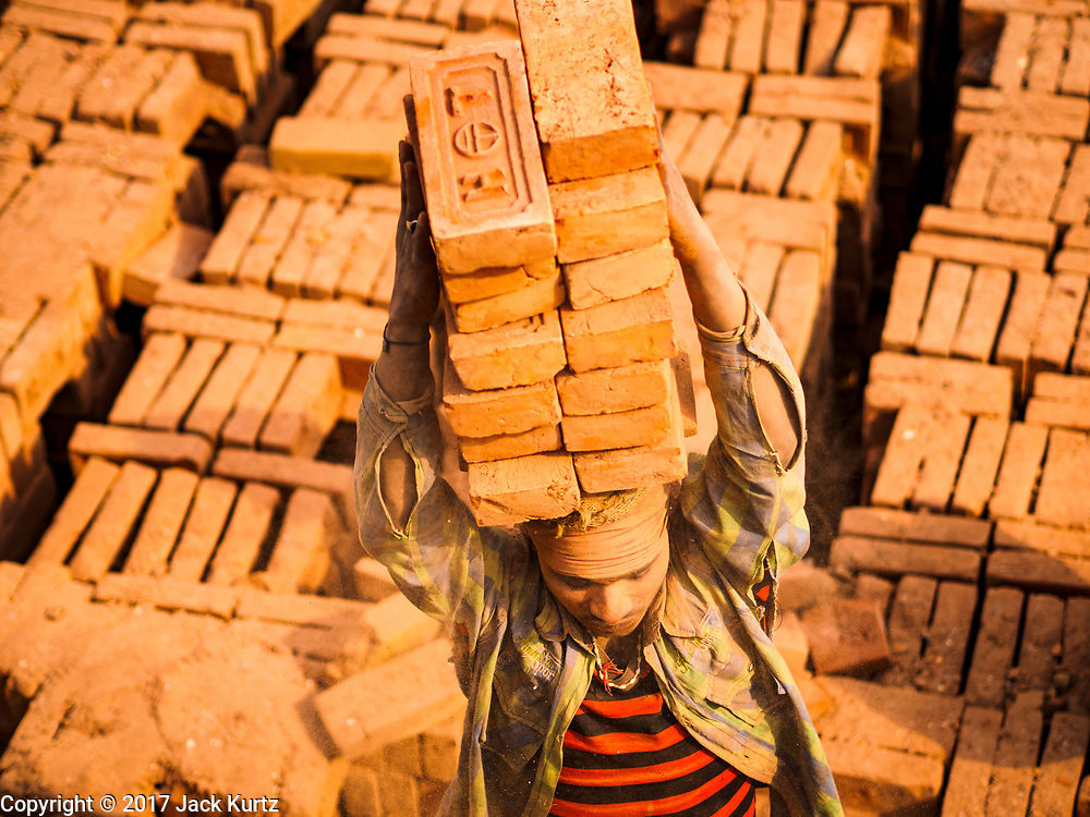 09 MARCH 2017 - BAGMATI, NEPAL: Workers take finished bricks out of a kiln at a brick factory in Bagmati, near Bhaktapur. There are almost 50 brick factories in the valley near Bagmati. The brick makers are very busy making bricks for the reconstruction of Kathmandu, Bhaktapur and other cities in the Kathmandu valley that were badly damaged by the 2015 Nepal Earthquake. The brick factories have been in the Bagmati area for centuries because the local clay is a popular raw material for the bricks. Most of the workers in the brick factories are migrant workers from southern Nepal.           PHOTO BY JACK KURTZ