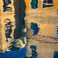 Reflections n the waterway canal of the incredibly colourful houses of the small island of Burano in the Venetian lagoon, part of the municipality of Venice.