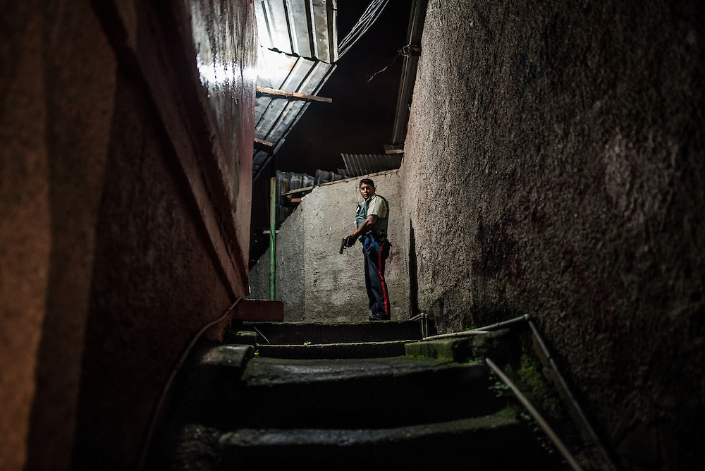 CARRIZAL, VENEZUELA - DECEMBER 10, 2016:  Police officers patrol a slum in Carrizal, Venezuela. A severe economic crisis in Venezuela, caused by the drop in oil prices and years of economic mismanagement under a Socialist government, has lead to an alarming rise in crime and insecurity in the country.  Hyperinflation has left both the working class and professional class of workers with salaries that cannot purchase enough food to feed their families. Many people are turning to crime to make ends meet.  PHOTO: Meridith Kohut for The New York Times