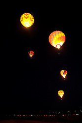"""Dawn Patrol 4"" - Photograph of lit up hot air balloons flying over Reno during Dawn Patrol at the 2011 Great Reno Balloon Race."