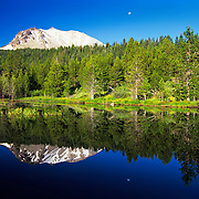 Lassen Peak and the moon reflect in Hat Lake in Lassen Volcanic National Park, CA.