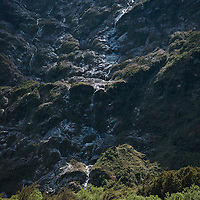 Water cascades over rocky mountainside, dwarfing walker nearby, Clinton Canyon, Milford Track, Fiordland, New Zealand
