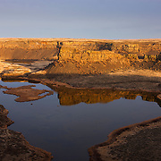 Dry Falls, located in Grant County, Washington, at one time was believed to be the largest waterfall that ever existed. Geologists believe that during the last ice age, ice dams resulted in giant glacial lakes in eastern Washington, Idaho and Montana. When those dams failed, as they did dozens of times, glacial lakes Columbia and Missoula rapidly drained, creating a cataclysmic flood. During the floods, what is now Dry Falls was a spectacular waterfall, 400 feet high (121 meters), 3.5 miles wide (5.63 kilometers). Water may have raced over its massive cliffs at 65 miles an hour (105 km/hour), a flow that's estimated to be ten times as powerful as all the world's current rivers combined. The cliffs shown here represent a small fraction of the ice age waterfall. Dry Falls Lake is pictured in the foreground; Green Lake is visible in the background.