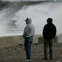 Plymouth, MA -  Perry Morneau (L) and Jim Seal watch the waves break over the sea wall at Town Beach in Plymouth on December 21, 2010.  The pair, who are down from Maine to work a construction project on Cape Cod had the day off because of the snow.  Photo by Matthew Healey