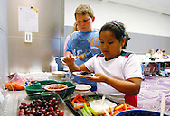 Zachary Frantzen (L) and Fernanda Garcia-Villanueva serve themselves healthy snacks after a graduation ceremony from the 10-week Shapedown Program at The Children's Hospital in Aurora, Colorado May 29, 2010.  The program is part of the child and teen weight management program at the hospital. REUTERS/Rick Wilking (UNITED STATES)