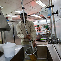 """A sudanese refugee  is washing dishes in the dairy kitchen  of the Royal Beach Hotel on February 28 2011. The municipality hung 1,500 red flags around the city as a sign of warning and put up hundreds of banners reading: """"Protecting our home, the residents of Eilat are drawing the line on infiltration."""" Eilat Mayor Meir Yitzhak Halevi said that 10 percent of the city's population was currently made up of migrants and that the residents feel that the city has been conquered...Photo by Olivier Fitoussi."""