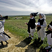 Sister Gail Fitzpatrick, abbess of Our Lady of the Mississippi Abbey, sprinkles Holy Water on the fields during The Blessing of the Fields service on St. Isidore's feast day near Dubuque, Iowa.  Left to right, Sisters Genevieve Durcun, Grace Remington and Kathleen O'Neill look on.  The community of 22 Roman Catholic nuns follow Jesus Christ through a life of prayer, silence, simplicity and ordinary work.  Their home is a beautiful monastery which sits high on a bluff, overlooking the Mississippi River.