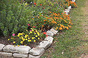 Flower bed in fall with rock edging.