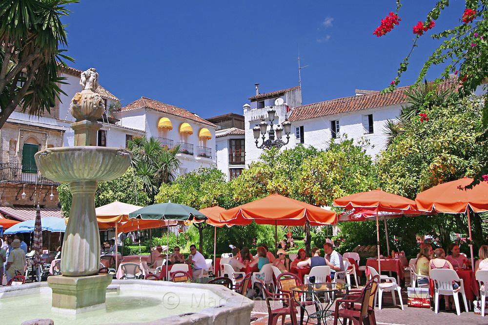 Fountain and people dining, Orange Square (Plaza de los Naranjos), Marbella Old Town, Costa Del Sol, Spain.