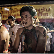 Devotees of the Chinese Shrine of Gim Tsu Ong, near Phuket, Thailand, work themselves into a trance prior to attending a fire walking ritual.