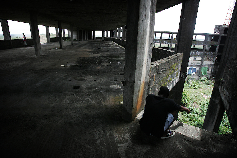 "A man sits 19 September 2005 on one of the many levels of the former uncompleted Ministry of National Defense building in Congo Town on the outskirts of Monrovia. The ""Pentagon"", named this way by its occupants, shelters 394 families totalling approximately 3,000 people who were booted out in May 2005 of the Barclay Training Center, which had been their home for the last two decades. Former soldiers, who fought for former Liberian presidents Samuel Doe and Charles Taylor, live in this building with no water or electricity, overcoming past differences. The construction of the building started in 1984 under Doe's leadership, and the war interrupted the its completion and later served as a base for Taylor's men."