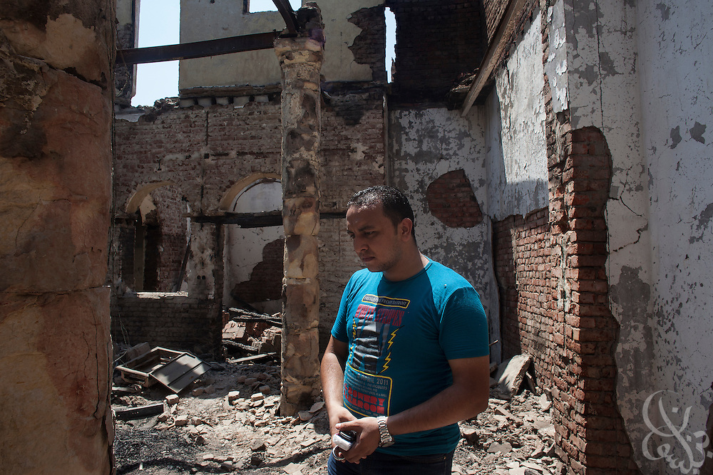 Deacon Ebraam surveys damage inside the ruins of the (old) Virgin Mary Church August 20, 2013 a week after an attack by Muslims in the village of Nazla, located near el Fayoum around a 100 kilometers South of Cairo, Egypt.  Christian villagers report 2 churches and a monastery in the area came under attack by their Muslim neighbors on the same day as Egyptian security forces were moving to forcibly disperse the sit-in camp of the supporters of deposed president Mohamed Morsi.
