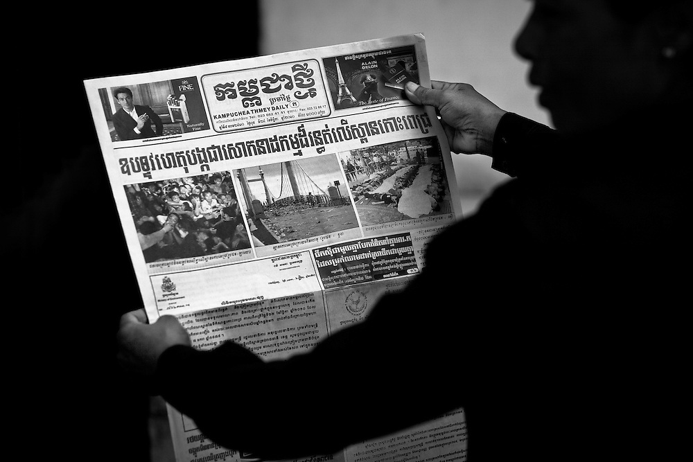 A woman reads the newspaper with images and stories of the previous days stampede outside Calmette Hospital in Phnom Penh, Cambodia where many of the victims of the stampede tragedy on November 22nd 2010 were brought.