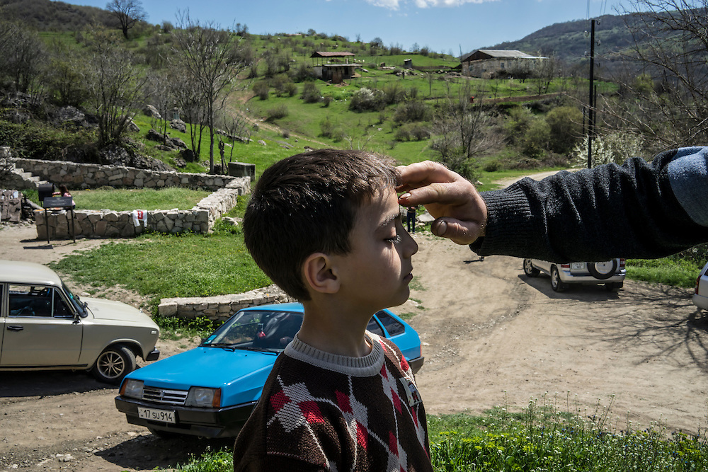 KARASHEN, NAGORNO-KARABAKH - APRIL 19: Aram Aslanyan, 6, has a cross marked on his forehead using the blood of a chicken which his family killed in sacrifice in order to bring good fortune on April 19, 2015 in Karashen, Nagorno-Karabakh. Since signing a ceasefire in a war with Azerbaijan in 1994, Nagorno-Karabakh, officially part of Azerbaijan, has functioned as a self-declared independent republic and de facto part of Armenia, with hostilities along the line of contact between Nagorno-Karabakh and Azerbaijan occasionally flaring up and causing casualties. (Photo by Brendan Hoffman/Getty Images) *** Local Caption *** Aram Aslanyan