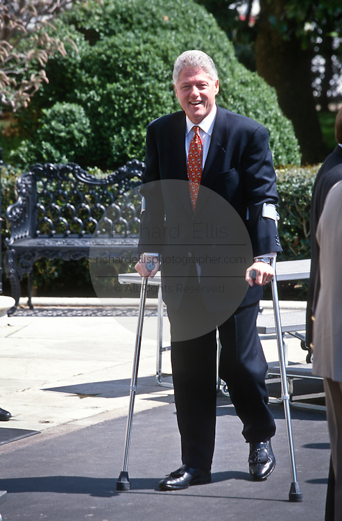 President Bill Clinton walks with crutches as he recovers from a knee injury  at the White House April 3, 1997.