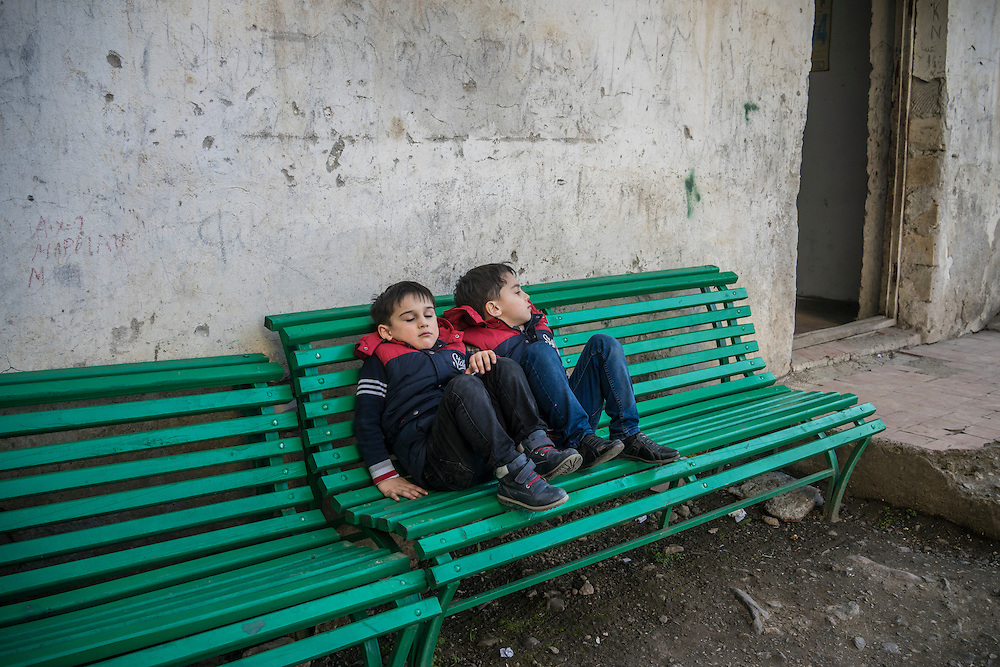 STEPANAKERT, NAGORNO-KARABAKH - APRIL 17: Boys sit on a bench behind a cluster of apartment buildings on February 21, 2015 in Stepanakert, Nagorno-Karabakh. Since signing a ceasefire in a war with Azerbaijan in 1994, Nagorno-Karabakh has functioned as a de facto part of Armenia, with hostilities along the line of contact between Nagorno-Karabakh and Azerbaijan occasionally flaring up and causing casualties. (Photo by Brendan Hoffman/Getty Images) *** Local Caption ***