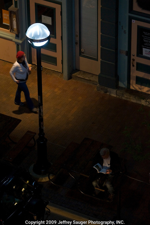 A man reads under an LED streetlight, made by Relume Technologies, Inc., E. Washington St. in Ann Arbor, MI, Thursday, May 7, 2009. Ann Arbor has installed LED streetlights to reduce lighting costs and greenhouse gas emissions.
