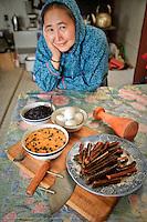 Martha Nicolai with traditional Yup'ik Eskimo foods in her kitchen in Kwethluk, Alaska. She uses an ulu and pestle to prepare berries, eggs, salmon strips, and aqutaq.