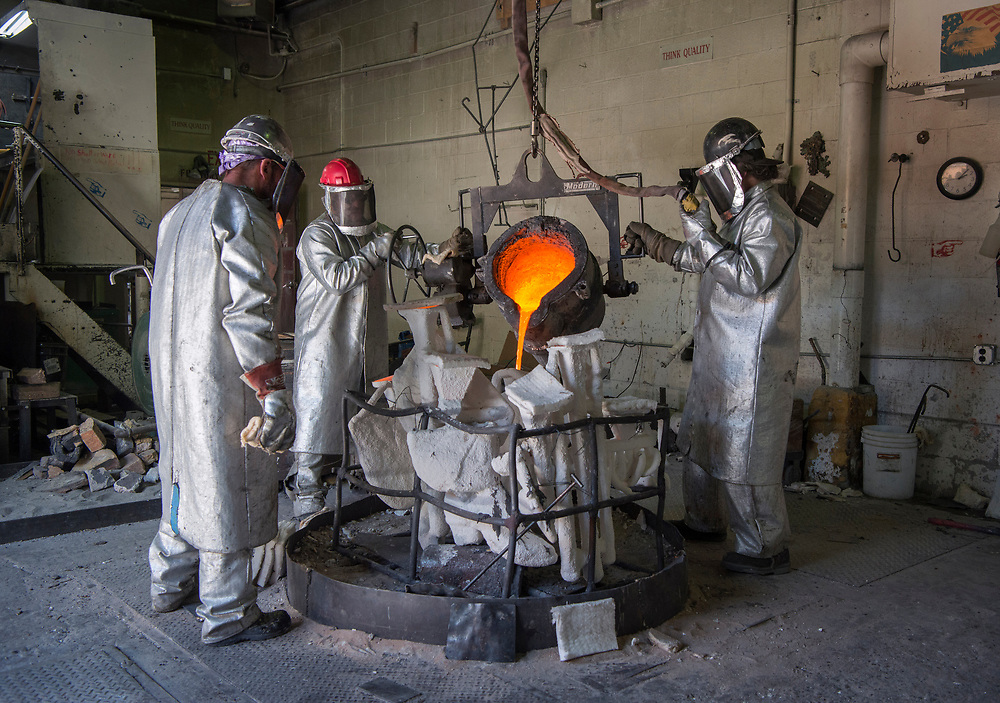 em041917o/jnorth/From left, David Miles, Josh Ybarra and Duwayne Blankley fill shells with molten bronze at the Shidoni Foundry in Tesuque, Wednesday April 19, 2017. When the workers have completed the orders Shidoni had the equipment will be moved to a new location in Albuquerque to become the Albuquerque Foundry.  (Eddie Moore/Albuquerque Journal