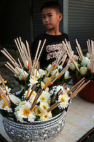 Thai Boy Selling Floral Temple Offerings. Lotus and marigolds are most popular, these offerings come with incense or joss sticks attached.
